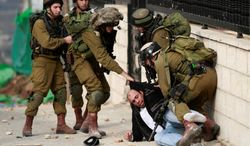"""Israeli soldiers arrest a Palestinian man outside his home during clashes between Palestinians and Israeli soldiers in Jalazoun refugee camp near the West Bank city of Ramallah, Friday, Feb. 14, 2014. """"The radicalization of the West Bank is going to get a lot worse,"""" said Samir Awad, a political scientist at Birzeit University near Ramallah. """"Many Palestinians are in despair at the continued Israeli occupation, settlement growth, failing peace talks and are turning to extremist solutions."""""""