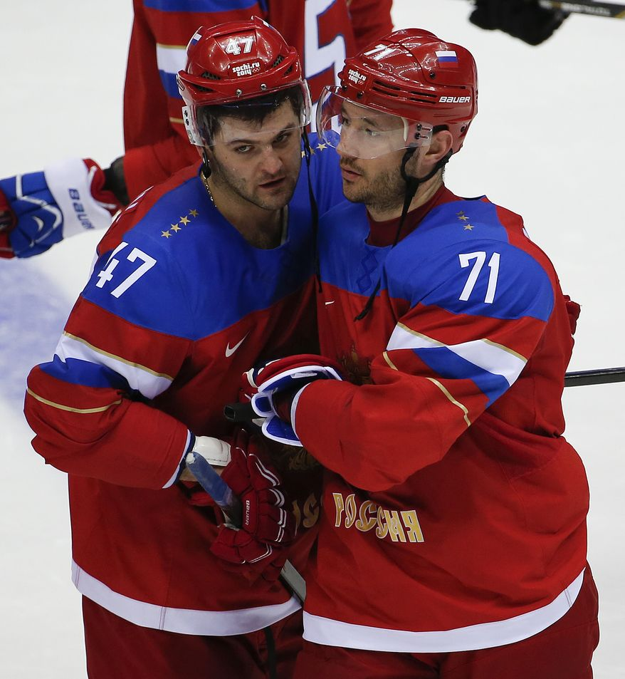 Russia forward Ilya Kovalchuk, right, is congratulated by Russia forward Alexander Radulov after hitting the winning shot in a shootout against Slovakia during a men's ice hockey game at the 2014 Winter Olympics, Sunday, Feb. 16, 2014, in Sochi, Russia. Russia won 1-0.  (AP Photo/Julio Cortez)