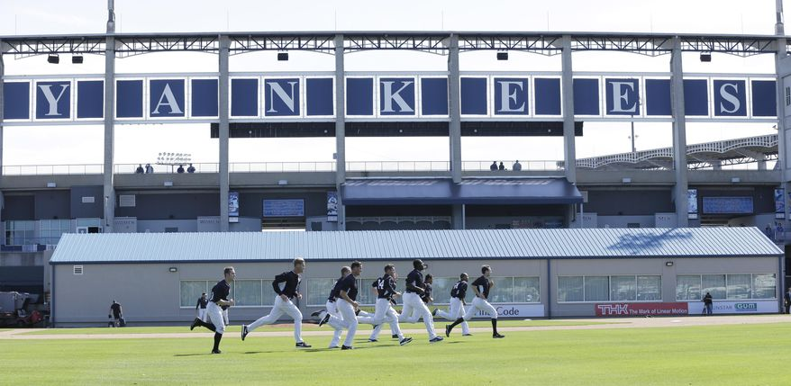 New York Yankees pitchers run on a practice field during spring training baseball practice Saturday, Feb. 15, 2014, in Tampa, Fla. (AP Photo/Charlie Neibergall)