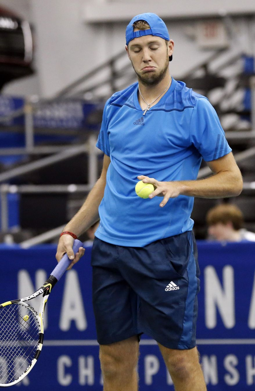 Jack Sock reacts to the serve of Ivo Karlovic, of Croatia, in the quarterfinal match at the U.S. National Indoor Tennis Championships, Friday, Feb. 14, 2014, in Memphis, Tenn. (AP Photo/Rogelio V. Solis)