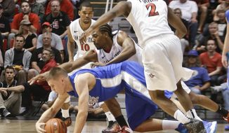 Air Force forward Marek Olesinski dives for a loose ball with San Diego State forward Josh Davis while trying to break through the San Diego State defense during the first half of an NCAA college basketball game Saturday, Feb. 15, 2014, in San Diego. (AP Photo/Lenny Ignelzi)