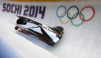 The two-man team from the United States USA-1, piloted by Steven Holcomb, speeds down the track during the men's two-man bobsled training at the 2014 Winter Olympics, Thursday, Feb. 13, 2014, in Krasnaya Polyana, Russia. (AP Photo/Natacha Pisarenko)