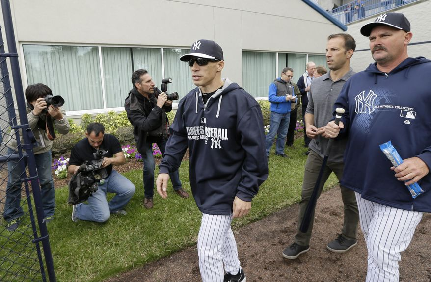 New York Yankees manager Joe Girardi, center, walks to the field before a spring training baseball practice Saturday, Feb. 15, 2014, in Tampa, Fla. (AP Photo/Charlie Neibergall)
