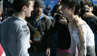 Yuzuru Hanyu of Japan, right, and Patrick Chan of Canada smile following the flower ceremony after the men's free skate figure skating final at the Iceberg Skating Palace at the 2014 Winter Olympics, Friday, Feb. 14, 2014, in Sochi, Russia. Hanyu placed first and Chan second. (AP Photo/Ivan Sekretarev)