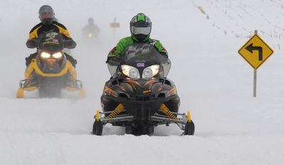Scott Wood, from Valparaiso, Ind., leads a group of snowmobilers as they approach Sink Road, west of Dowagiac, Mich., during a ride Saturday, Feb. 15, 2014. (AP Photo/The Herald-Palladium, Don Campbell)