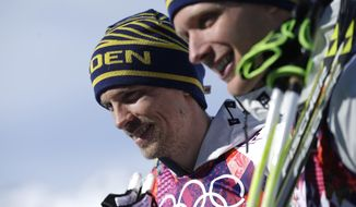 Silver medalist Sweden's Johan Olsson, left, and Sweden's Daniel Richardsson, who took the bronze, pose following the flowers ceremony for the men's 15K classical-style cross-country race at the 2014 Winter Olympics, Friday, Feb. 14, 2014, in Krasnaya Polyana, Russia. (AP Photo/Gregorio Borgia)