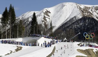 Competitors ski past the Olympic rings during the women's 4x5K cross-country relay at the 2014 Winter Olympics, Saturday, Feb. 15, 2014, in Krasnaya Polyana, Russia. (AP Photo/Kirsty Wigglesworth)