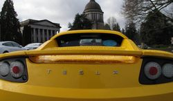A Tesla car is parked near the Washington state Capitol on Monday, Feb. 17, 2014, in Olympia, Wash. The electric car company, which has sales and service operations in Seattle and Bellevue, held a rally to protest measures being considered by the Legislature that would prevent it from opening additional facilities in the state. (AP Photo/Rachel La Corte)
