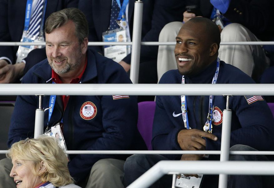 San Francisco 49ers tight end Vernon Davis, right, attends women's curling competition at the 2014 Winter Olympics, Saturday, Feb. 15, 2014, in Sochi, Russia. Davis was named honorary captain of the Men's U.S. Olympic Curling team for the 2010 Winter Olympics in Vancouver. (AP Photo/Robert F. Bukaty)