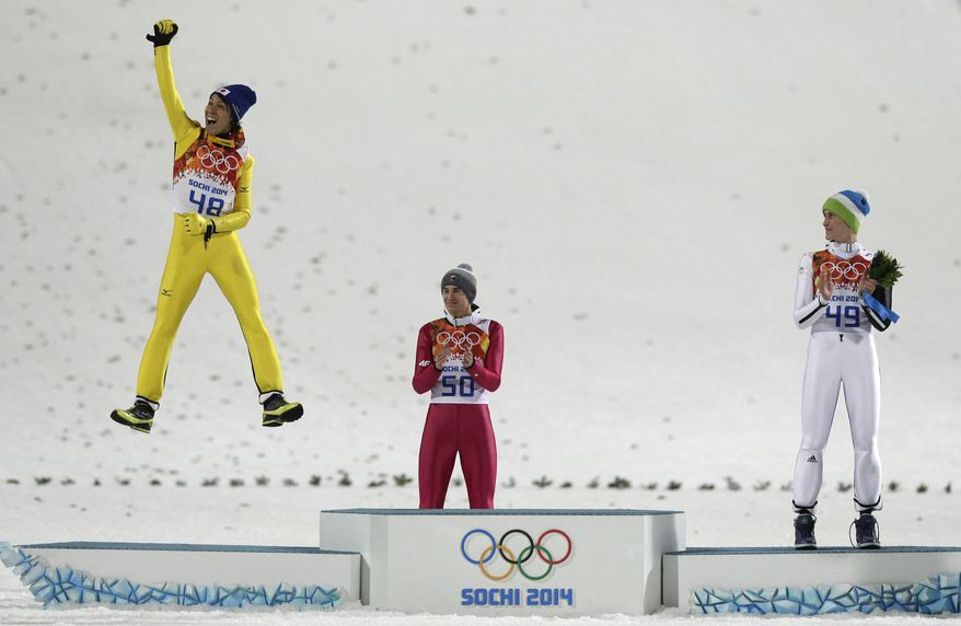 Japan's Noriaki Kasai celebrates winning the silver as Poland's gold medal winner Kamil Stoch and Slovenia's bronze medal winner Peter Prevc, from left, applaud during the flower ceremony after the ski jumping large hill final at the 2014 Winter Olympics, Saturday, Feb. 15, 2014, in Krasnaya Polyana, Russia.(AP Photo/Matthias Schrader)