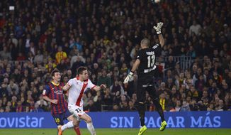 FC Barcelona's Lionel Messi, from Argentina, left, scores against Rayo Vallecano's goalkeeper Ruben Martinez, right, during a Spanish La Liga soccer match at the Camp Nou stadium in Barcelona, Spain, Saturday, Feb. 15, 2014. (AP Photo/Manu Fernandez)