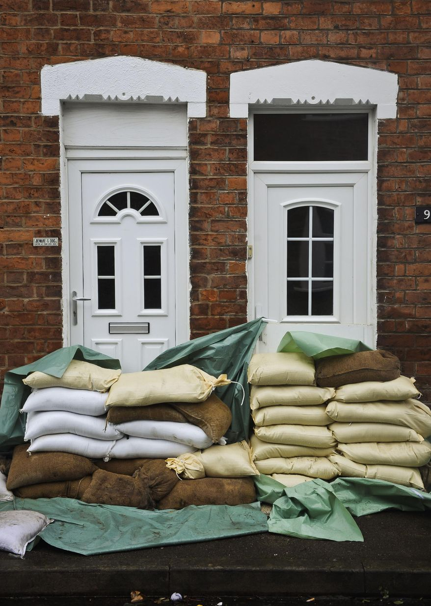 Sandbags form a levee protecting the front doors of homes in Gloucester, southwest England, as the region reacts to an increased flood threat alert Friday Feb. 14, 2014.  Many regions of Britain have been warned to expect severe weather over the coming days from heavy rainfall, gale-force winds and snow.(AP Photo/Ben Birchall, PA) UNITED KINGDOM OUT - NO SALES - NO ARCHIVES