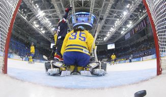 Lyndsey Fry of the United States celebrates Megan Bozek's goal as Goalkeeper Valentina Wallner of Sweden sits on her knees during the second period of the 2014 Winter Olympics women's semifinal ice hockey game at Shayba Arena, Monday, Feb. 17, 2014, in Sochi, Russia. (AP Photo/Bruce Bennett, Pool)