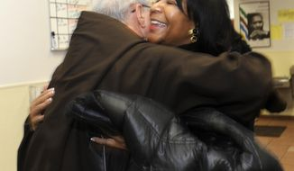 Father Jerry Smith and General Motors Foundation President Vivian Pickard embrace at the Capuchin Soup Kitchen in Detroit, on Monday, Feb. 17, 2014. The GM Foundation is donating $1 million among three Detroit nonprofits in honor of retired GM Chairman and CEO Dan Akerson and his wife Karin, who were major benefactors to nonprofit organizations during their time in Detroit. The foundation on Monday is making stops at the three charities: Capuchin Soup Kitchen, Habitat for Humanity Detroit and the Coalition On Temporary Shelter, presenting them each with checks. Capuchin Soup Kitchen received $500,000 to help feed more in need, while Habitat is receiving $400,000 to aid its effort to renovate and build new homes in the city. The shelter will get $100,000 to provide services to the homeless and help them become self sufficient. (AP Photo/Detroit News, David Coates)