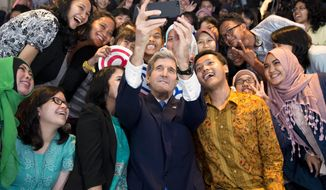 "Secretary of State John Kerry takes a selfie with a group of students before delivering a speech on climate change on Sunday, Feb. 16, 2014, in Jakarta, Indonesia. Climate change may be the world's ""most fearsome"" weapon of mass destruction and urgent global action is needed to combat it, Kerry said on Sunday, comparing those who deny its existence or question its causes to people who insist the Earth is flat. (AP Photo/ Evan Vucci, Pool)"