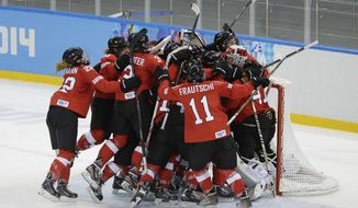 Team Switzerland celebrates their 2-0 victory over Russia during the 2014 Winter Olympics women's ice hockey quarterfinal game at Shayba Arena, Saturday, Feb. 15, 2014, in Sochi, Russia. (AP Photo/Matt Slocum)