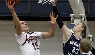 Saint Mary's Beau Levesque, left, shoots against BYU's Nate Austin (33) in the first half of an NCAA college basketball game on Saturday, Feb. 15, 2014, in Moraga, Calif. (AP Photo/Ben Margot)
