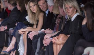 British model Suki Waterhouse, centre left, and her boyfriend U.S actor Bradley Cooper, centre right, watch the show by Tom Ford during London Fashion Week Autumn/Winter 2014, at Lindley Hall in central London, Monday, Feb. 17, 2014. (Photo by Joel Ryan/Invision/AP)
