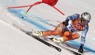 Norway's Aksel Lund Svindal passes a gate in the men's super-G at the Sochi 2014 Winter Olympics, Sunday, Feb. 16, 2014, in Krasnaya Polyana, Russia. (AP Photo/Charles Krupa)