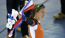 Bronze medallist Lotte van Beek of the Netherlands holds her national flag and celebrates past Dutch band Kleintje Pils, or Little Beer, wearing clogs, after the women's 1,500-meter race at the Adler Arena Skating Center during the 2014 Winter Olympics in Sochi, Russia, Sunday, Feb. 16, 2014. (AP Photo/David J. Phillip )