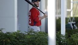 Boston Red Sox second baseman Dustin Pedroia holds a bat as he departs the clubhouse during spring training baseball practice, Monday, Feb. 17, 2014, in Fort Myers, Fla. (AP Photo/Steven Senne)