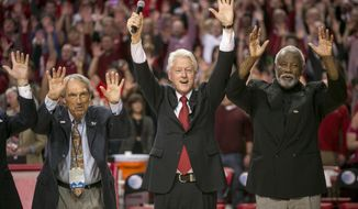 "Eddie Sutton, left, former President Bill Clinton, center, and Nolan Richardson, right, call the ""Hogs"" during halftime of an NCAA college basketball game between Arkansas and LSU on Saturday, Feb. 15, 2014, in Fayetteville, Ark. (AP Photo/Gareth Patterson)"