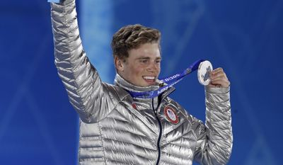 Men's slopestyle skiing silver medalist Gus Kenworthy of the United States smiles while holding his medal during the medals ceremony at the 2014 Winter Olympics, Thursday, Feb. 13, 2014, in Sochi, Russia. (AP Photo/Morry Gash)