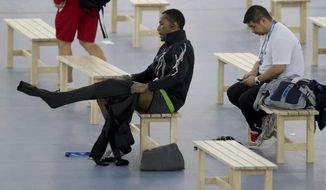 Shani Davis of the U.S., center, puts on the prototype of the official US Speedskating suit, while coach Ryan Shimabukuro checks his phone prior to a training session at the Adler Arena Skating Center at the 2014 Winter Olympics, Friday, Feb. 14, 2014, in Sochi, Russia. The team thought it had a chance to do something special, given some impressive World Cup results this season and new high-tech suits from Under Armour, which got an assist in the design from aerospace giant Lockheed Martin. Now, there's plenty of grumbling that the suits are actually slowing the skaters down in Sochi. (AP Photo/Matt Dunham)