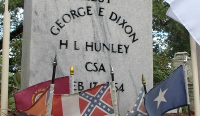 FILE - Flags adorn the grave of Confederate Lt. George Dixon, the commander of the Confederate submarine H.L. Hunley, in Charleston, S.C., in this Feb. 17, 2012, file photo. Monday, Feb. 17, 2014, is the 150th anniversary of the attack in which the Hunley sank the Union blockade ship Housatonic off Charleston, S.C., during the Civil War, becoming the first submarine in history to sink an enemy warship. (AP Photo/Bruce Smith, File)