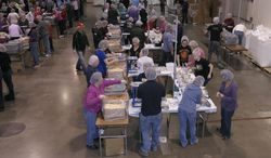 In this Feb. 14, 2014 photo, volunteers pack food for the malnourished during the 2 Million Meals event, in Novi, Mich. More than 8,000 people helped pack 2 million-plus meals, which will be shipped to El Salvador, Haiti and the Philippines. Here, volunteers from NorthRidge Church are shown at one of the packing stations. (AP Photo/Detroit News, Clarence Tabb Jr.)
