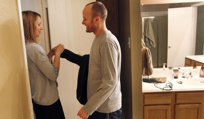 In a Feb. 12, 2014 photo, Kam Manthe, left, helpsher husband Jason change his clothes for bed at their home in McKinney, Texas. Jason, 37, has been diagnosed with early-onset Alzheimer's disease. And Kam now cares all for four children as well as Jason.  (AP Photo/The Dallas Morning News, Kye R. Lee)
