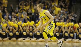 CORRECTS MARQUETTE PLAYER TO JAKE THOMAS, INSTEAD OF STEVE TAYLOR JR. - Marquette's Jake Thomas reacts after he made a 3-point basket against Xavier during the second half of an NCAA college basketball game Saturday, Feb. 15, 2014, in Milwaukee. (AP Photo/Jeffrey Phelps)