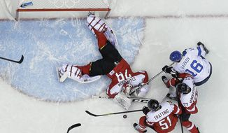Austria goaltender Bernhard Starkbaum reaches for the rebound as Finland forward Aleksander Barkov looks to score in the third period of a men's ice hockey game at the 2014 Winter Olympics, Thursday, Feb. 13, 2014, in Sochi, Russia. (AP Photo/Mark Humphrey )