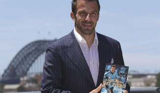 """FILE - In this Nov. 21, 2013 file photo, Sydney FC captain Alessandro Del Piero of Italy poses with his new book """"Playing on"""" for photographers during the launch of his autobiography in Sydney, Australia. Del Piero will play against former club Juventus for the first time after agreeing to join an A-League All Stars side for a football friendly against the Serie A champion in August. (AP Photo/Rob Griffith, File)"""