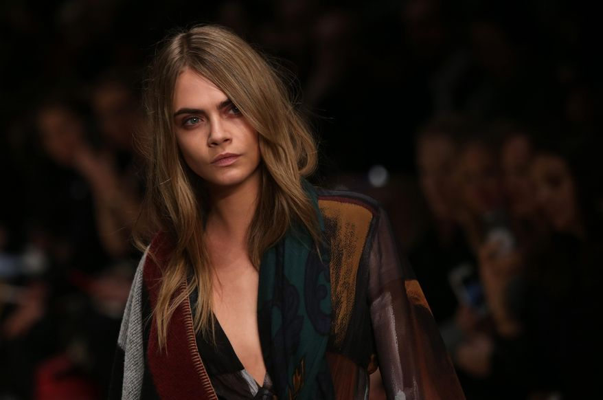 Model Cara Delevingne wears a design created by Burberry Prorsum Womenswear during London Fashion Week Autumn/Winter 2014, at Perks Field, Kensington Palace, in Hyde Park, central London, Monday, Feb. 17, 2014. (Photo by Joel Ryan/Invision/AP)