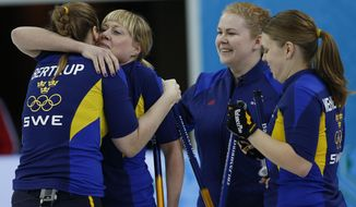 Sweden's women's curling team from left to right, Christina Bertrup, Maria Prytz, Margaretha Sigfridsson and Maria Wennerstroem, celebrate after beating Russia during the women's curling match at the 2014 Winter Olympics, Sunday, Feb. 16, 2014, in Sochi, Russia. (AP Photo/Wong Maye-E)