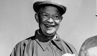 """President Eisenhower wears a big smile, and a button to match, which reads, """"Don't ask what I shot,"""" at his golf match with Sen. Robert A. Taft of Ohio at Augusta National Country Club, Augusta, GA, April 20, 1953.  The button was handed to the chief executive by a newsman shortly before he reached the first tee for his match with Taft.  (AP Photo/William J. Smith)"""