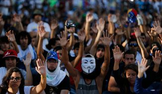 Demonstrators hold up their hands during a protest in Caracas, Venezuela, Sunday, Feb. 16, 2014. Demonstrators are protesting the Wednesday killings of two university students who were shot in different incidents after an anti-government protest demanding the release of student protesters arrested in various parts of the country. (AP Photo/Fernando Llano)