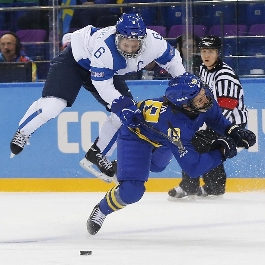 Jenni Hiirikoski of Finland (6) and Maria Lindh of Sweden collide during the 2014 Winter Olympics women's quarterfinal ice hockey game at Shayba Arena, Saturday, Feb. 15, 2014, in Sochi, Russia. (AP Photo/Petr David Josek)