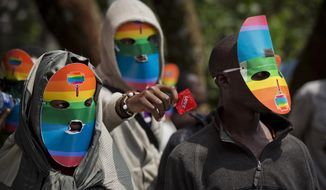 "FILE - In a Monday, Feb. 10, 2014 file photo, Kenyan gays and lesbians and others supporting their cause wear masks to preserve their anonymity and one holds out a wrapped condom, as they stage a rare protest, against Uganda's increasingly tough stance against homosexuality in solidarity with their counterparts there, outside the Uganda High Commission in Nairobi, Kenya. President Barack Obama says in a statement provided Sunday, Feb. 15, 2014 that pending steps by Uganda to further criminalize homosexuality will complicate what he is describing as America's valued relationship with the East African nation. Museveni said Friday that he plans to sign a bill into law that prescribes life imprisonment for what they term as ""aggravated"" homosexual acts.(AP Photo/Ben Curtis)"