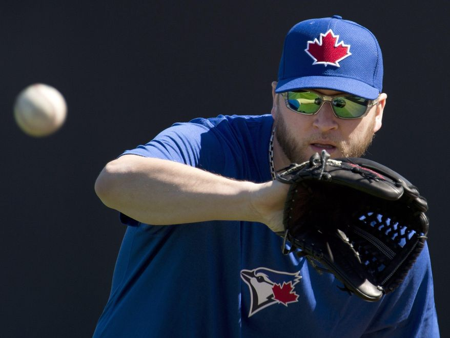 Toronto Blue Jays pitcher Mark Buehrle catches a ball at the stadium during spring training baseball in Dunedin, Fla., Sunday, Feb. 16, 2014. (AP Photo/The Canadian Press, Frank Gunn)