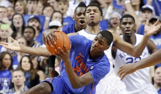 Florida's DeVon Walker, bottom, is fouled by Kentucky's Andrew Harrison during the second half of an NCAA college basketball game Saturday, Feb. 15, 2014, in Lexington, Ky. Florida won 69-59. (AP Photo/James Crisp)