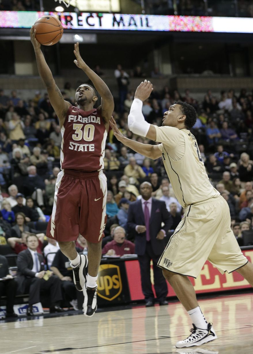 Florida State's Ian Miller (30) drives past Wake Forest's Devin Thomas (2) during the second half of an NCAA college basketball game in Winston-Salem, N.C., Saturday, Feb. 15, 2014. Florida State won 67-60. (AP Photo/Chuck Burton)