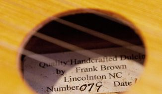ADVANCE FOR TUESDAY FEB. 18 - This Jan. 2, 2014 photo shows a label inside one of Frank Brown's handmade dulcimers in Lincolnton, N.C. Lincolnton resident Frank Brown likes knowing he can take a piece of wood that would have otherwise been cut up or used to build a barn, he said, and turn it into an object that produces a beautiful sound. For the last eight years, the 72-year-old has been crafting handmade dulcimers at his home. (AP Photo/Lincoln Times News, Jaclyn Anthony)