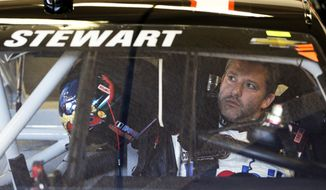 Driver Tony Stewart adjusts the rear view mirror in his car before going out on the track to practice for the NASCAR Sprint Unlimited auto race at Daytona International Speedway in Daytona Beach, Fla., Friday, Feb. 14, 2014.  Stewart has not raced in more than six months since he broke two bones in his leg in an August 2013 sprint-car crash.(AP Photo/John Raoux)