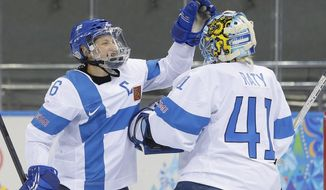 Jenni Hiirikoski of Finland celebrates their 2-1 win over Germany with goalkeeper Noora Raty after the 2014 Winter Olympics women's ice hockey game at Shayba Arena, Sunday, Feb. 16, 2014, in Sochi, Russia. (AP Photo/Matt Slocum)
