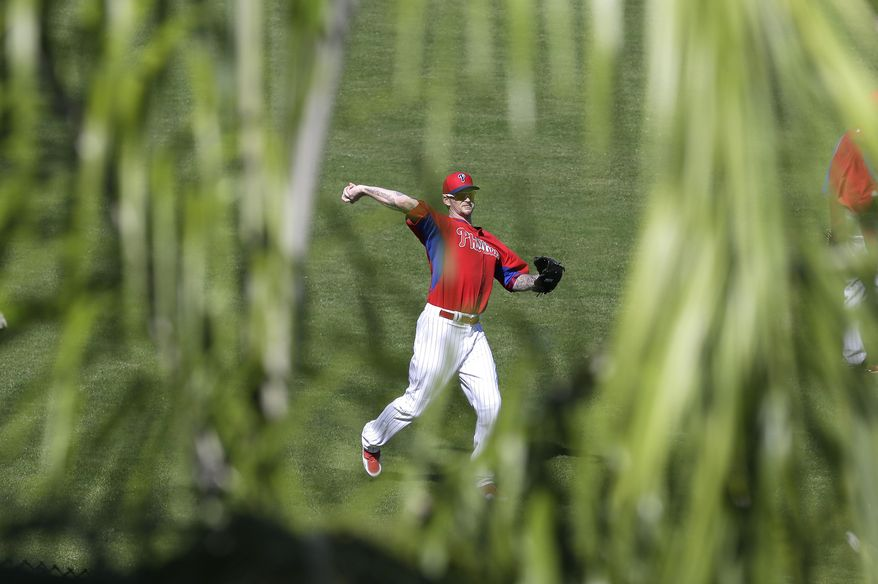 Philadelphia Phillies pitcher A.J. Burnett throws in the outfield during spring training baseball practice on Sunday, Feb. 16, 2014, in Clearwater, Fla. (AP Photo/Charlie Neibergall)