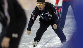 U.S. coach Ryan Shimabukuro urges on one of his athletes competing in the women's 1,500-meter speedskating race at the Adler Arena Skating Center during the 2014 Winter Olympics in Sochi, Russia, Sunday, Feb. 16, 2014. (AP Photo/Patrick Semansky)