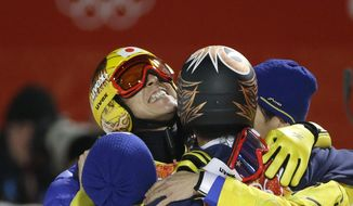 Japan's Noriaki Kasai, left, celebrates winning the silver after the ski jumping large hill final at the 2014 Winter Olympics, Saturday, Feb. 15, 2014, in Krasnaya Polyana, Russia. (AP Photo/Gregorio Borgia)