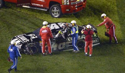 Jimmie Johnson is helped out of his car after it colliding with the inside wall on the front stretch during the Sprint Unlimited auto race at Daytona International Speedway in Daytona Beach, Fla., Saturday, Feb. 15, 2014. (AP Photo/Phelan M. Ebenhack)